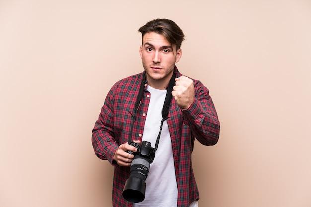 拳、攻撃的な表情を示す孤立した若い白人写真家の男。