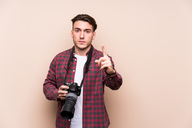 若い白人写真家の男が指でナンバーワン表示を分離しました。