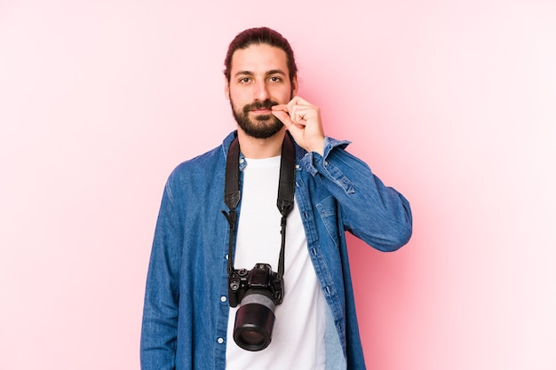 Young caucasian photographer man isolated with fingers on lips keeping a secret.