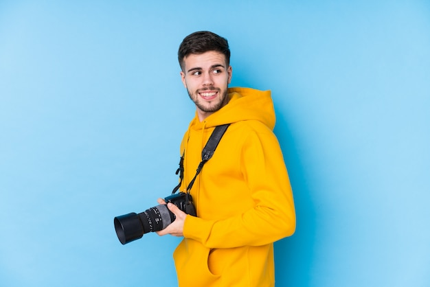 Young caucasian photographer man looks aside smiling, cheerful and pleasant.