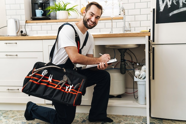 アパートで働いている間、機器とクリップボードを備えた制服の保持バッグに若い白人の配管工の男