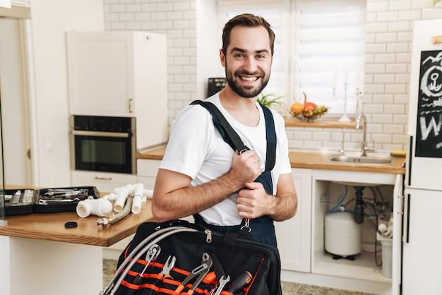 制服を着た若い白人配管工の男がアパートで働いている間、笑顔で装備のバッグを保持