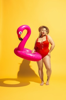 Young caucasian plus size female model's preparing for beach resort on yellow