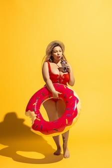 Il giovane modello femminile caucasico plus size si sta preparando per la località balneare su giallo