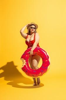 젊은 백인 더하기 크기 여성 모델의 노란색 벽에 휴가 준비. 빨간 수영복과 모자 수영 포즈에 여자.