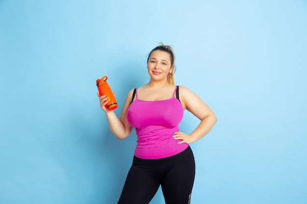 Giovane caucasico plus size modello femminile di formazione su sfondo blu. concetto di sport, emozioni umane, espressione, stile di vita sano, corpo positivo, uguaglianza. in posa con bottiglia, copyspace.