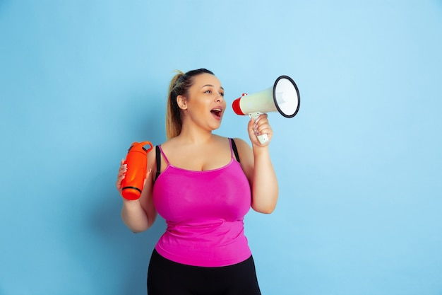 Young caucasian plus size female model's training on blue background. concept of sport, human emotions, expression, healthy lifestyle, body positive, equality. posing with bottle and mouthpeace.