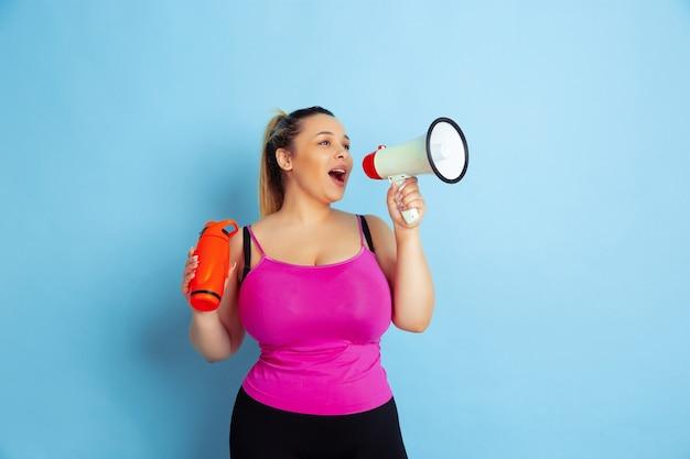 Giovane caucasico plus size modello femminile di formazione su sfondo blu. concetto di sport, emozioni umane, espressione, stile di vita sano, corpo positivo, uguaglianza. in posa con bottiglia e boccale.