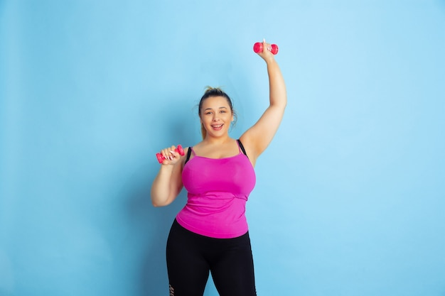 Young caucasian plus size female model's training on blue background. concept of sport, human emotions, expression, healthy lifestyle, body positive, equality. training with the weights, copyspace.