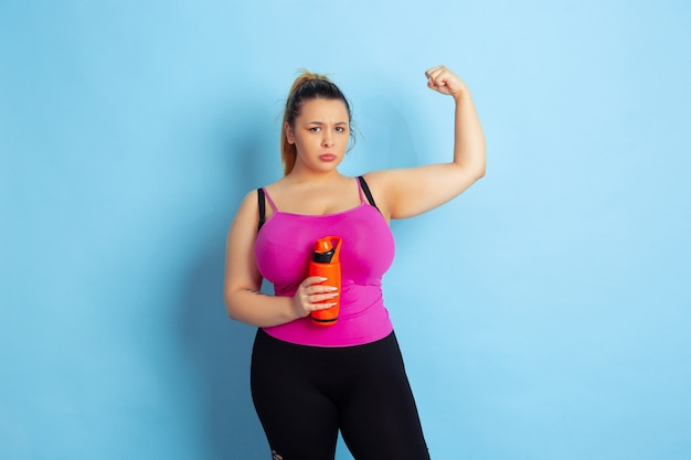 Young caucasian plus size female model's training on blue space
