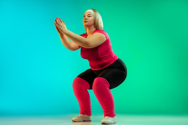Young caucasian plus size female model's training on gradient green background in neon light. doing workout exercises, stretching, cardio. concept of sport, healthy lifestyle, body positive, equality.