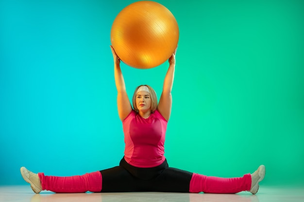 Young caucasian plus size female model's training on gradient green background in neon light. doing workout exercises with the fitball. concept of sport, healthy lifestyle, body positive, equality.