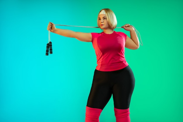 Young caucasian plus size female model's training on gradient green background in neon light. doing workout exercises with jump rope. concept of sport, healthy lifestyle, body positive, equality.