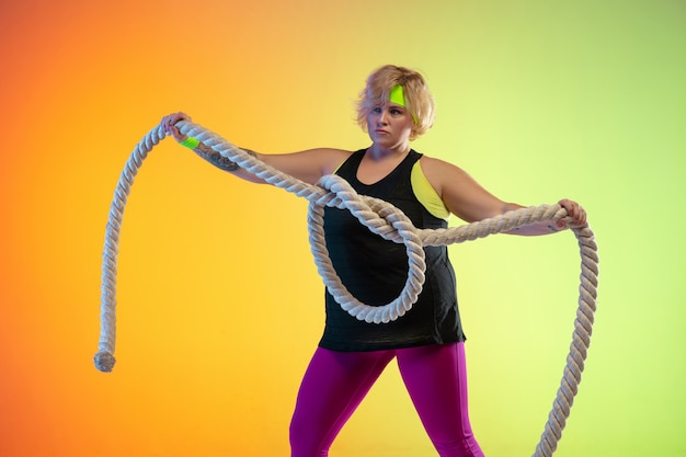 Young caucasian plus size female model's training on gradient orange background in neon light. doing workout exercises with the ropes. concept of sport, healthy lifestyle, body positive, equality.