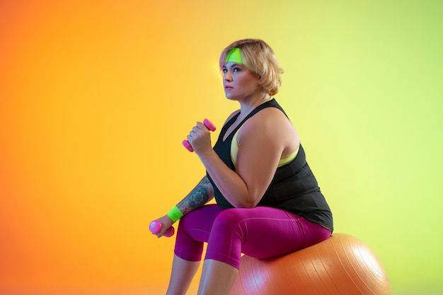 Young caucasian plus size female model's training on gradient orange background in neon light. doing workout exercises with the weights. concept of sport, healthy lifestyle, body positive, equality.