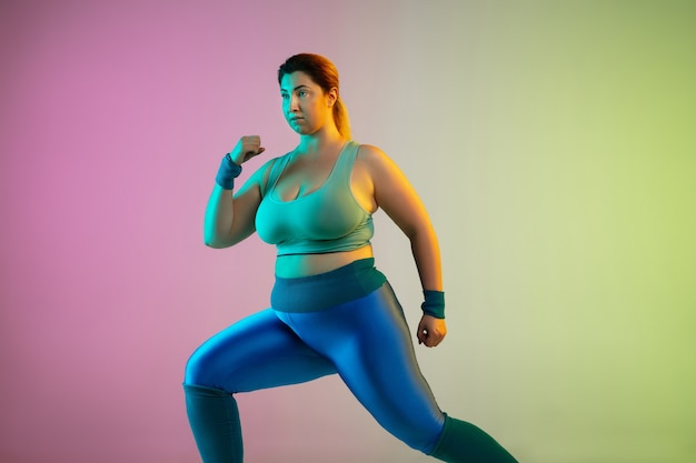 Young caucasian plus size female model's training on gradient purple green wall in neon. doing stretching workout exercises.