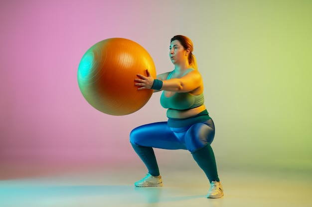 Young caucasian plus size female model's training on gradient purple green wall in neon light. doing workout exercises with fitball.