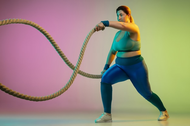 Young caucasian plus size female model's training on gradient purple green wall in neon light. doing workout exercises with ropes. concept of sport, healthy lifestyle, body positive, equality.