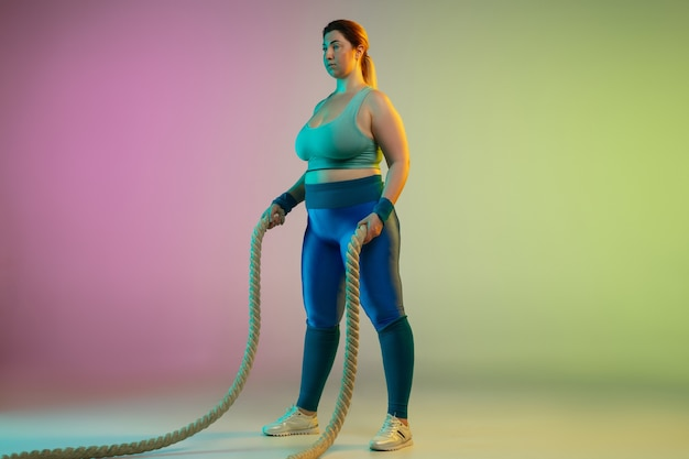 Young caucasian plus size female model's training on gradient purple green wall in neon light. doing workout exercises with ropes.
