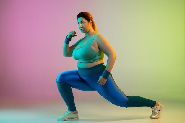 Giovane modello femminile caucasico plus size allenamento su parete verde viola sfumata
