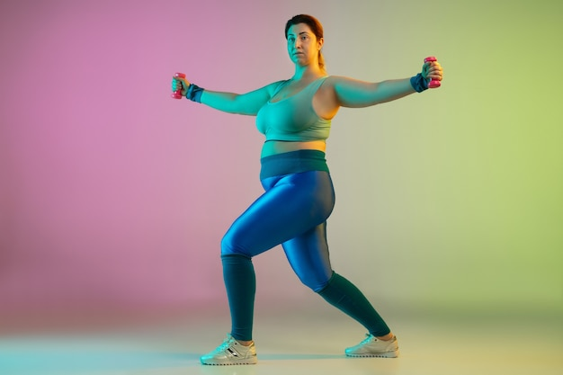 Young caucasian plus size female model's training on gradient purple green wall