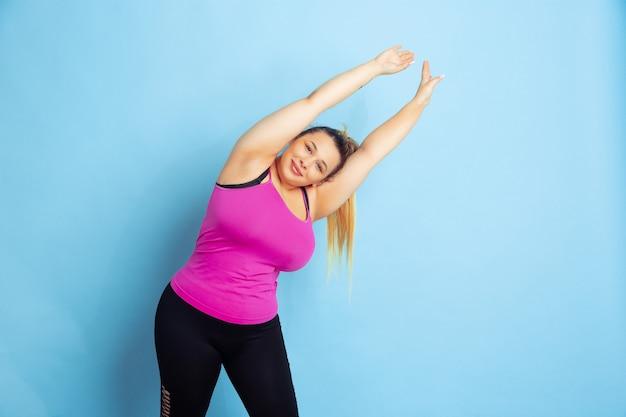 青の背景に若い白人プラスサイズの女性モデルのトレーニング。スポーツの概念、人間の感情、表現、健康的なライフスタイル、ボディポジティブ、平等。ストレッチ体操をする。