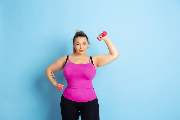 青の背景に若い白人プラスサイズの女性モデルのトレーニング。スポーツの概念、人間の感情、表現、健康的なライフスタイル、ボディポジティブ、平等。重み、コピースペースを使用したトレーニング。