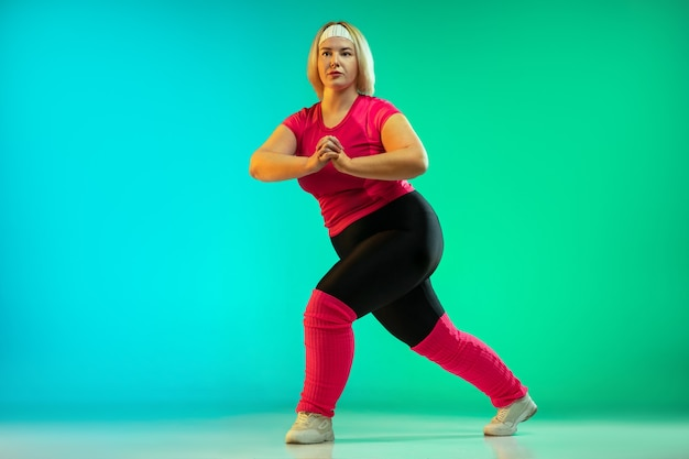 ネオンの光の中で緑のグラデーションの背景に若い白人のプラスサイズの女性モデルのトレーニング。エクササイズ、ストレッチ、有酸素運動を行う。スポーツのコンセプト、健康的なライフスタイル、ポジティブな体、平等。