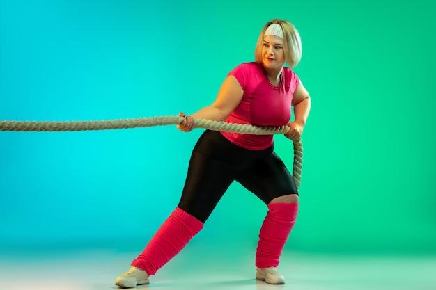 ネオンの光の中で緑のグラデーションの背景に若い白人のプラスサイズの女性モデルのトレーニング。ロープを使ってエクササイズを行います。スポーツのコンセプト、健康的なライフスタイル、ポジティブな体、平等。