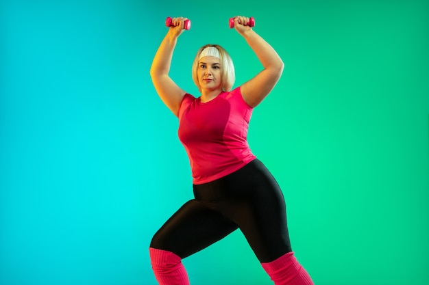 ネオンの光の中でグラデーションの緑の背景に若い白人プラスサイズの女性モデルのトレーニング。ウェイトを使ってトレーニングを行う。スポーツ、健康的なライフスタイル、ボディポジティブ、平等の概念。