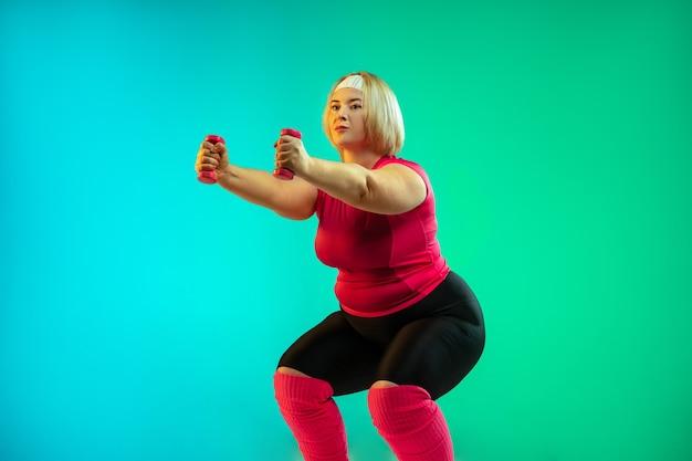 ネオンの光の中で緑のグラデーションの背景に若い白人のプラスサイズの女性モデルのトレーニング。ウェイトを使ってエクササイズを行います。スポーツのコンセプト、健康的なライフスタイル、ポジティブな体、平等。