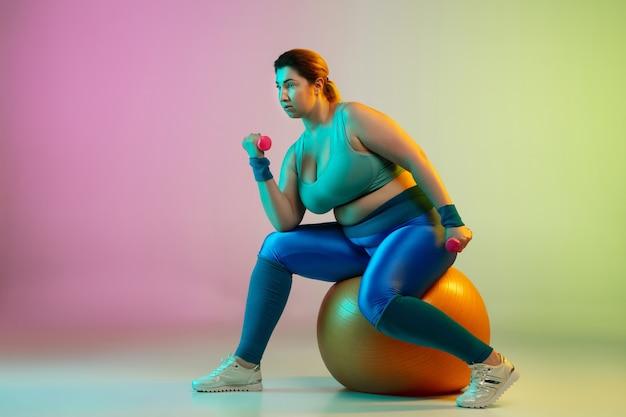 ネオンの光の中でグラデーション紫緑の壁に若い白人プラスサイズの女性モデルのトレーニング。ウエイトを使ってトレーニングエクササイズをする。スポーツ、健康的なライフスタイル、ボディポジティブ、平等の概念。