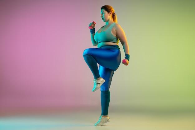 그라데이션 보라색 녹색 벽에 젊은 백인 플러스 사이즈 여성 모델의 훈련
