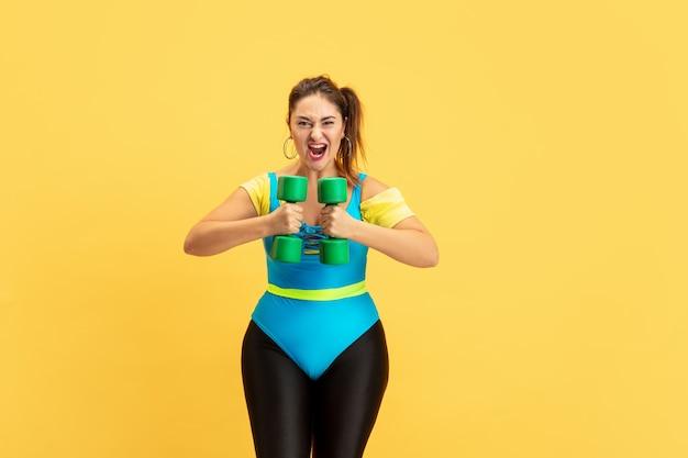 노란색 배경에 젊은 백인 더하기 크기 여성 모델의 교육. copyspace. 스포츠, 건강한 라이프 스타일, 신체 긍정적, 패션, 스타일의 개념. 세련 된 여자 감정적 인 무게 연습.