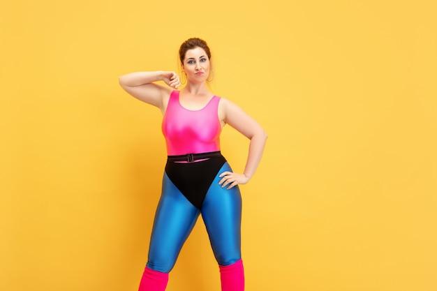 黄色い背景に若い白人プラスサイズの女性モデルのトレーニング。コピースペース。スポーツのコンセプト、健康的なライフスタイル、ポジティブなボディ、ファッション、スタイル。スタイリッシュな女性が自信を持ってクールにポーズをとる。