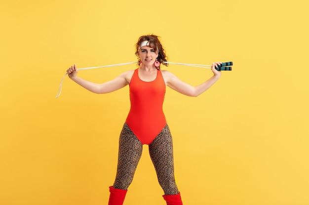 黄色い背景に若い白人プラスサイズの女性モデルのトレーニング。コピースペース。スポーツのコンセプト、健康的なライフスタイル、ポジティブなボディ、ファッション、スタイル。縄跳びの練習をするスタイリッシュな女性。