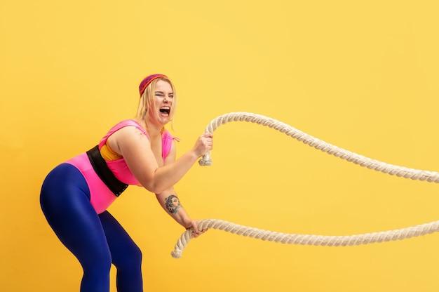 黄色い背景に若い白人プラスサイズの女性モデルのトレーニング。コピースペース。スポーツのコンセプト、健康的なライフスタイル、ポジティブなボディ、ファッション、スタイル。ロープを持ったスタイリッシュな女性が叫びます。