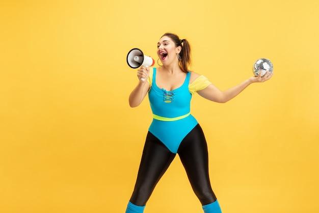 黄色い背景に若い白人プラスサイズの女性モデルのトレーニング。明るい服を着たスタイリッシュな女性。コピースペース。スポーツのコンセプト、健康的なライフスタイル、ポジティブなボディ、ファッション。ディスコボールで呼び出します。