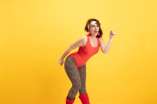 黄色い背景に若い白人プラスサイズの女性モデルのトレーニング。明るい服を着たスタイリッシュな女性。コピースペース。スポーツのコンセプト、健康的なライフスタイル、ポジティブなボディ、ファッション。柔軟なポージング。