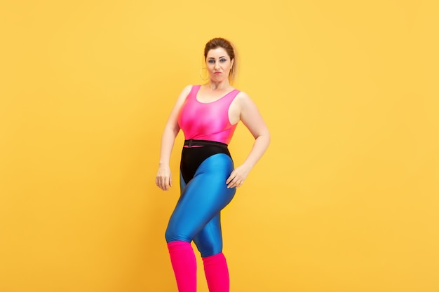 노란색 벽에 젊은 백인 더하기 크기 여성 모델의 교육. copyspace. 스포츠, 건강한 라이프 스타일, 신체 긍정적, 패션, 스타일의 개념. 자신감과 멋진 포즈 세련 된 여자.