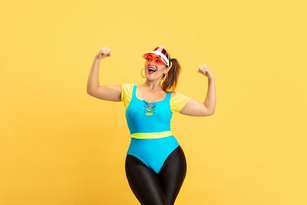 노란색 벽에 젊은 백인 더하기 크기 여성 모델의 교육. copyspace. 스포츠, 건강한 라이프 스타일, 신체 긍정적, 패션, 스타일의 개념. 자신감, 소녀 파워 포즈 세련 된 여자.