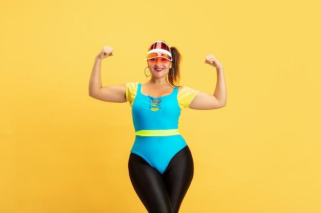 黄色い壁の若い白人プラスサイズの女性モデルのトレーニング。コピースペース。スポーツ、健康的なライフスタイル、ボディポジティブ、ファッション、スタイルの概念。自信を持ってポーズをとるスタイリッシュな女性、女の子の力。