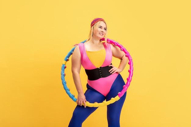 노란색 벽에 젊은 백인 더하기 크기 여성 모델의 교육. copyspace. 스포츠, 건강한 라이프 스타일, 신체 긍정적, 패션, 스타일의 개념. 밝은 후프와 함께 연습하는 세련 된 여자.