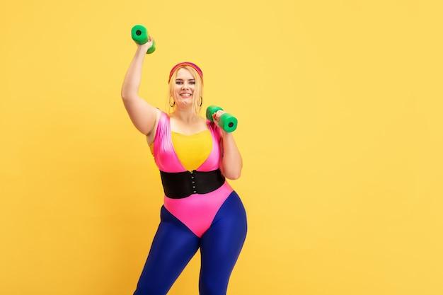 노란색 벽에 젊은 백인 더하기 크기 여성 모델의 교육. copyspace. 스포츠, 건강한 라이프 스타일, 신체 긍정적, 패션, 스타일의 개념. 녹색 무게로 연습하는 세련 된 여자.