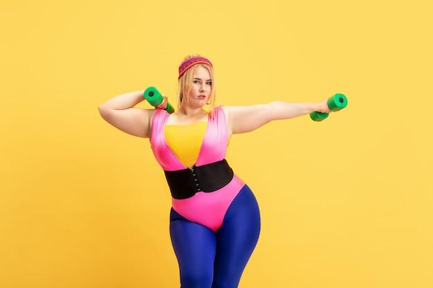 黄色い壁の若い白人プラスサイズの女性モデルのトレーニング。コピースペース。スポーツ、健康的なライフスタイル、ボディポジティブ、ファッション、スタイルの概念。緑の重みで練習しているスタイリッシュな女性。