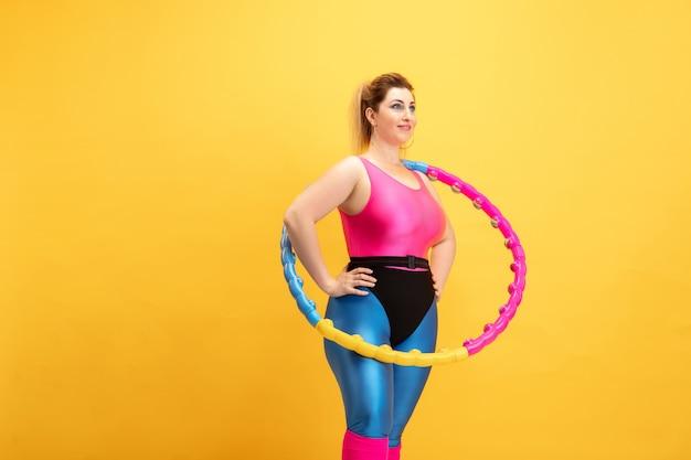 黄色い壁の若い白人プラスサイズの女性モデルのトレーニング。コピースペース。スポーツ、健康的なライフスタイル、ボディポジティブ、ファッション、スタイルの概念。フープと笑顔で練習しているスタイリッシュな女性。