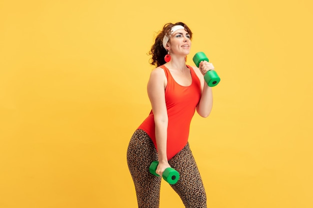 노란색 벽에 젊은 백인 더하기 크기 여성 모델의 교육. copyspace. 스포츠, 건강한 라이프 스타일, 신체 긍정적, 패션, 스타일의 개념. 무게와 연습하는 세련 된 여자.