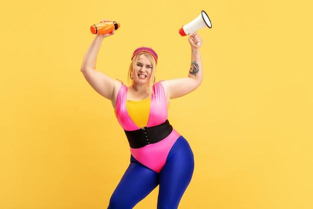 노란색 벽에 젊은 백인 더하기 크기 여성 모델의 교육. copyspace. 스포츠, 건강한 라이프 스타일, 신체 긍정적, 패션, 스타일의 개념. 병 및 mouthpeace와 세련 된 여자입니다.
