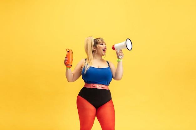 노란색 벽에 젊은 백인 더하기 크기 여성 모델의 교육. 밝은 옷에 세련 된 여자입니다. copyspace. 스포츠, 건강한 라이프 스타일, 신체 긍정적, 패션의 개념. 마우스 피스를 불러.