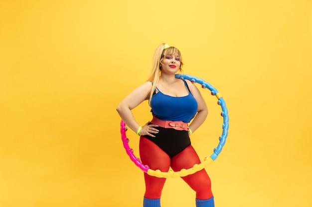 노란색 벽에 젊은 백인 더하기 크기 여성 모델의 교육. 밝은 옷에 세련 된 여자입니다. copyspace. 스포츠, 건강한 라이프 스타일, 신체 긍정적, 패션의 개념. 후프와 함께 포즈.